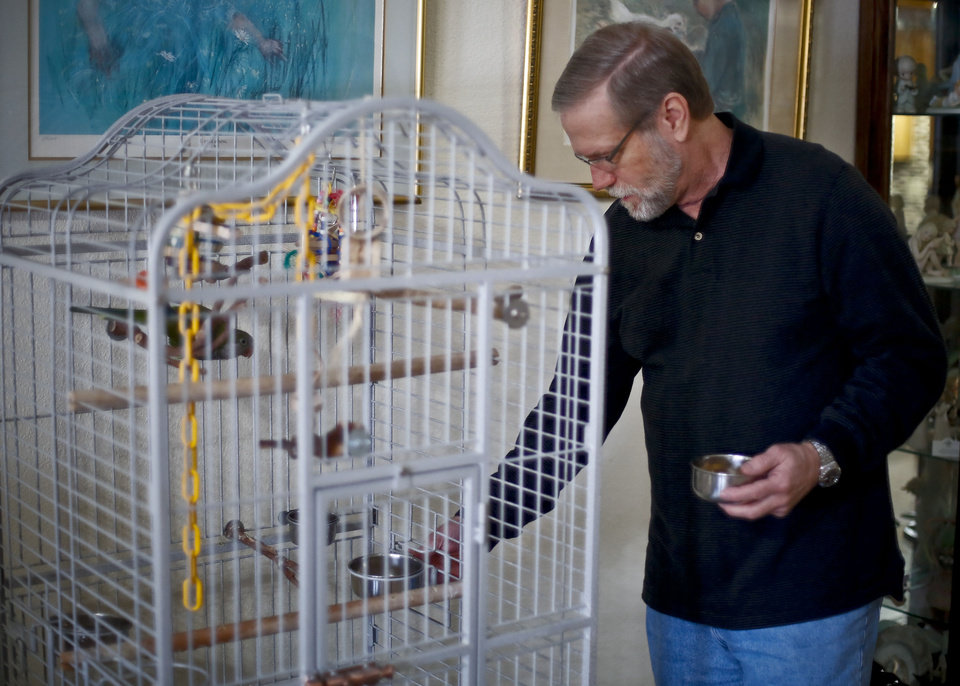 Photo - Alzheimers patient Ron Grant feeds his pet bird while at his home in Moore, Okla., Thursday, Dec. 12, 2013.  Grant was diagnosed in Oct. 2007, after noticing some lapses in his memory. Coming to peace with the outcome of his diagnosis, Grant says he does not want to live a long time with this. Grant's biggest concern is for his wife Vicky , 'If I live long enough for things to get bad, what will this do to her.' he says. Photo by Chris Landsberger, The Oklahoman