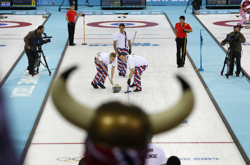 Photo - Norwegian curling fan Rune Eikeland, wearing viking horns, watches his countrymen Haavard Vad Petersson, left, and Christoffer Svae sweep in front of a rock delivered by  skip Thomas Ulsrud during men's curling competition against China at the 2014 Winter Olympics, Friday, Feb. 14, 2014, in Sochi, Russia. (AP Photo/Robert F. Bukaty)