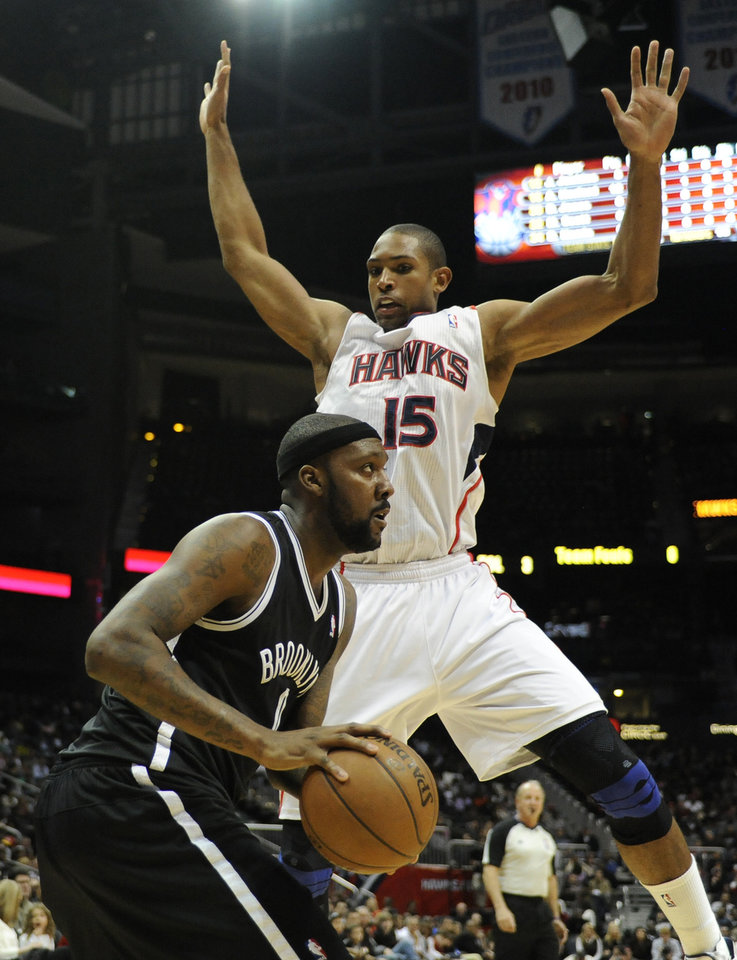 Photo - Brooklyn Nets' Andray Blatche looks to pass as Alanta Hawks' Al Horford (15) defends in the second half of an NBA basketball game at Philips Arena in Atlanta, Saturday, March 9, 2013. Brooklyn won 93-80. (AP Photo/David Tulis)