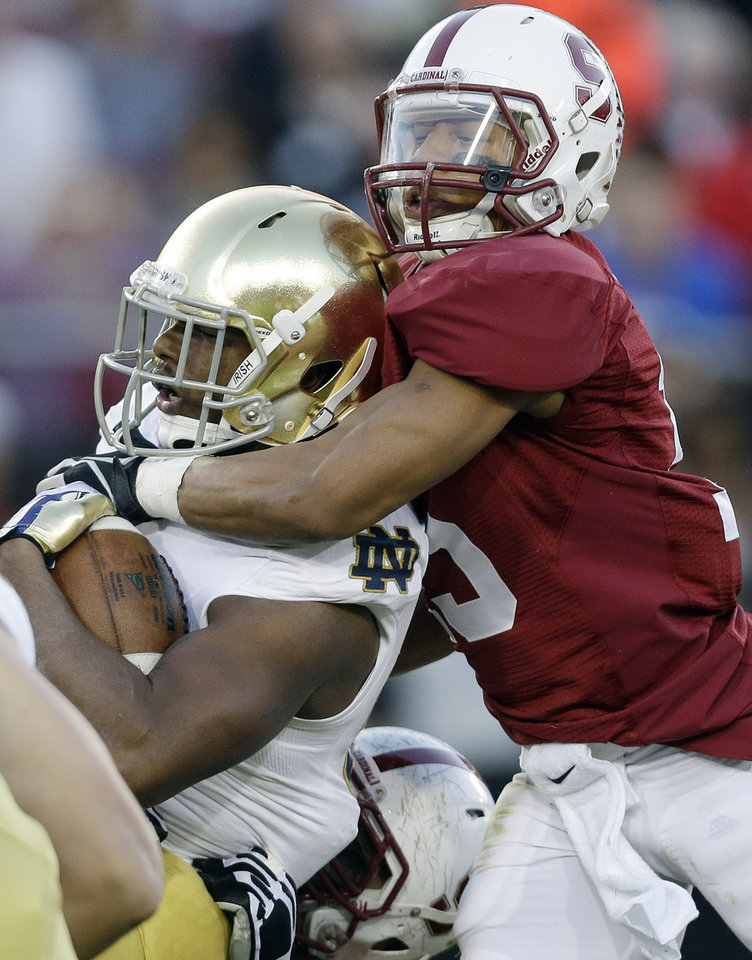 Photo - Notre Dame running back Tarean Folston, left, is tackled by Stanford defensive back Usua Amanam during the first half of an NCAA college football game on Saturday, Nov. 30, 2013, in Stanford, Calif. (AP Photo/Marcio Jose Sanchez)