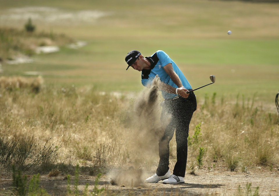 Photo - Dustin Johnson hits out of the native area on the 14th hole during the first round of the U.S. Open golf tournament in Pinehurst, N.C., Thursday, June 12, 2014. (AP Photo/Charlie Riedel)