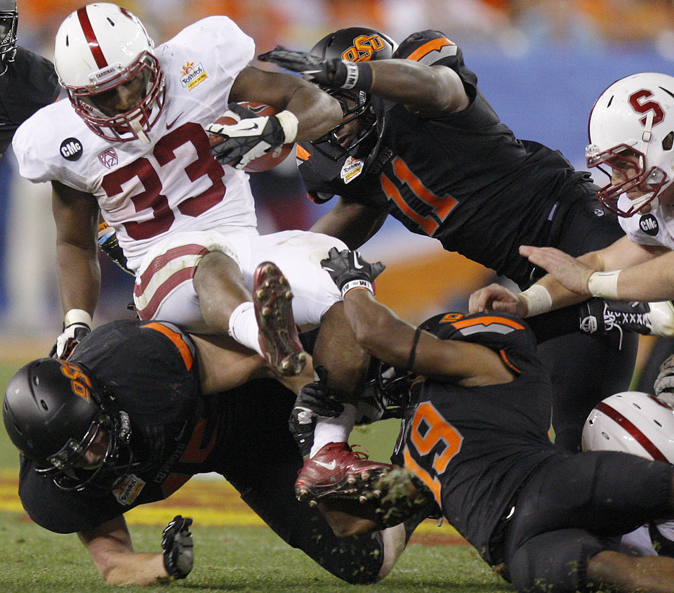 Photo - Stanford's Stepfan Taylor (33) is brought down by Oklahoma State's Caleb Lavey (45), Brodrick Brown (19), and Shaun Lewis (11) during the Fiesta Bowl between the Oklahoma State University Cowboys (OSU) and the Stanford Cardinal at the University of Phoenix Stadium in Glendale, Ariz., Monday, Jan. 2, 2012. Photo by Bryan Terry, The Oklahoman