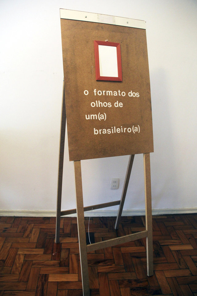 "Photo - In this May 2014 photo provided by Yudi Rafael Koike, a wooden easel mounted with a mirror, one of his installation, is displayed. Below the mirror is written: ""This is the shape of the Brazilian eyes."" ""Any shape of eyes,"" 28-year-old artist Koike says, ""is the shape of Brazilian eyes."" (AP Photo/Yudi Rafael Koike)"