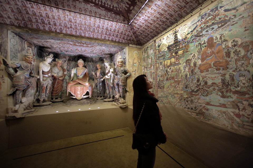 Photo - A woman views a full scale replica cave from the 8th century that contains the Bodhisattva of the Mogao Caves, in