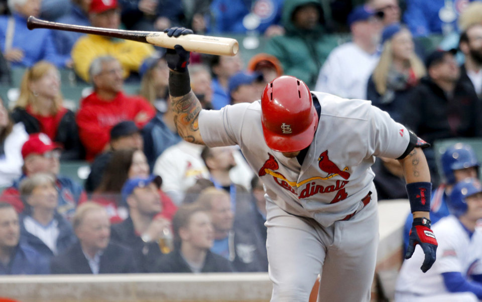 Photo - St. Louis Cardinals' Yadier Molina slams his bat to the ground after flying out with Matt Holliday on-base during the eighth inning of a baseball game against the Chicago Cubs, Friday, May 2, 2014, in Chicago. The Cubs won 6-5. (AP Photo/Charles Rex Arbogast)