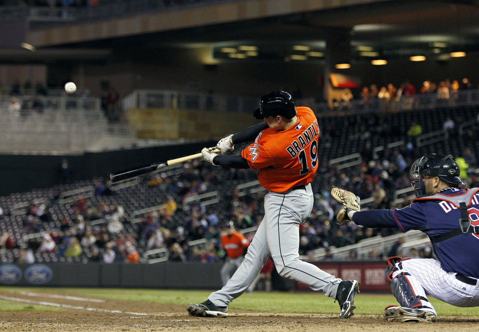 Photo - Miami Marlins catcher Rob Brantly (19) hits an RBI double against Minnesota Twins starting pitcher Mike Pelfrey (37) during the fifth inning in the second baseball game of a doubleheader Tuesday, April 23, 2013, in Minneapolis. (AP Photo/Genevieve Ross)