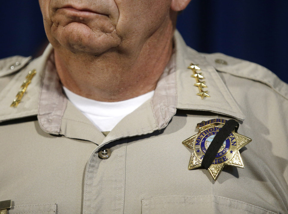Photo - Las Vegas Sheriff Doug Gillespie wears a black band across his badge during a news conference, Monday, June 9, 2014, in Las Vegas. Police say two police officers, along with a bystander, were killed by suspects Jerad and Amanda Miller yesterday. (AP Photo/John Locher)