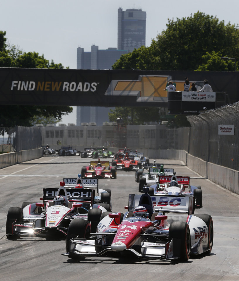 Photo - Takuma Sato (14), of Japan, leads the field into turn one on a restart during the second race of the IndyCar Detroit Grand Prix auto racing doubleheader in Detroit Sunday, June 1, 2014. (AP Photo/Paul Sancya)