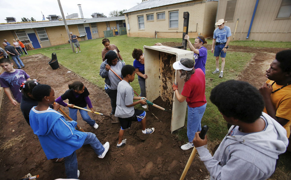 Photo - A trailer filled with topsoil is emptied. Volunteers are planting a garden at Stanley Hupfeld Academy at Western Village. Photo by Jim Beckel, The Oklahoman.  Jim Beckel