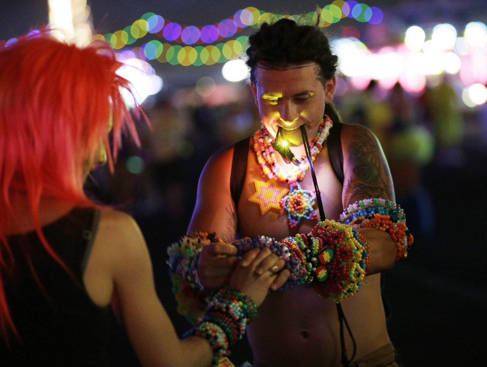 Photo - Two festival goers exchange beaded bracelets during the Electric Daisy Carnival, Friday, June 20, 2014, in Las Vegas. Many of the attendees make the bracelets, known as