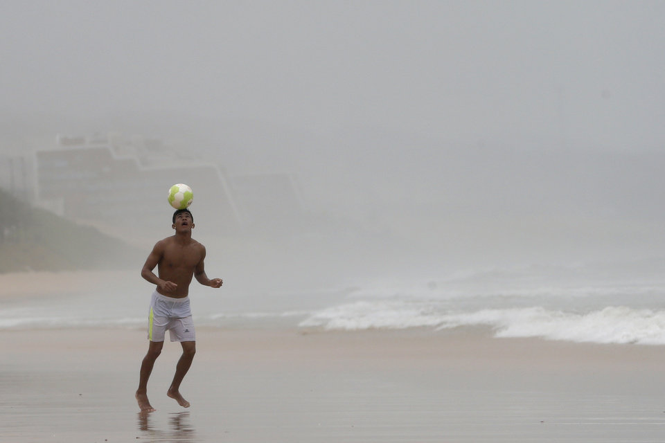 Photo - A man heads a soccer ball during a stroll along the beach on a rainy day in Natal, Brazil, Saturday, June 14, 2014. Natal is one of 12 cities hosting games during the 2014 World Cup soccer tournament. (AP Photo/Julio Cortez)