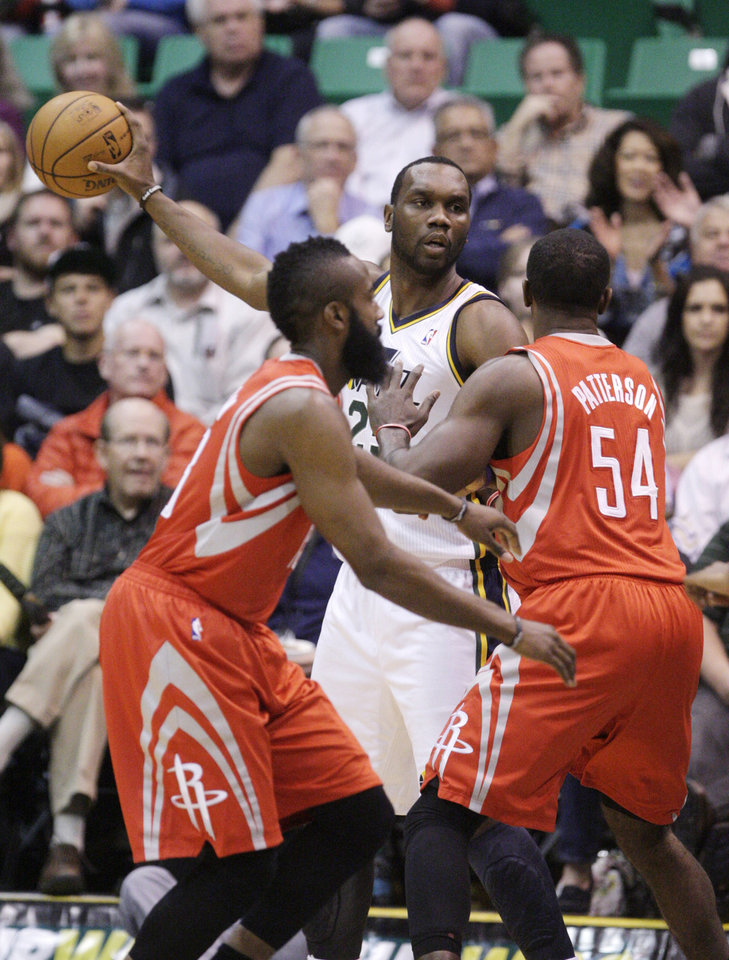 Houston Rockets guard James Harden, left, and forward Patrick Patterson (54) guard\ Utah Jazz center Al Jefferson, center, during the first quarter of an NBA basketball game Monday, Nov. 19, 2012, in Salt Lake City. (AP Photo/Rick Bowmer)