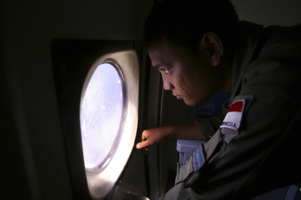 Photo - An Indonesian Navy crew member scans the water bordering Indonesia, Malaysia and Thailand during a search operation for the missing Malaysian Airlines Boeing 777 near the Malacca straits on Monday, March 10, 2014. Dozens of ships and aircraft have failed to find any piece of the missing Boeing 777 jet that vanished more than two days ago above waters south of Vietnam as investigators pursued