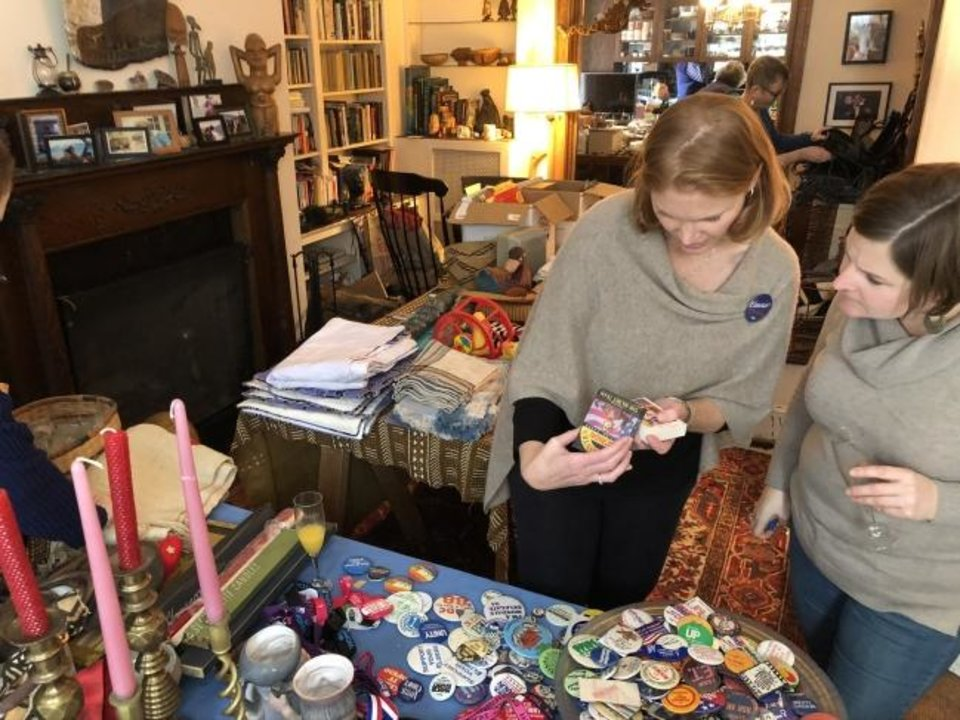 Photo -  Friends of Karen Mulhauser go through decades of political memorabilia at her downsizing party on Capitol Hill in Washington, D.C. [PETULA DVORAK/THE WASHINGTON POST]