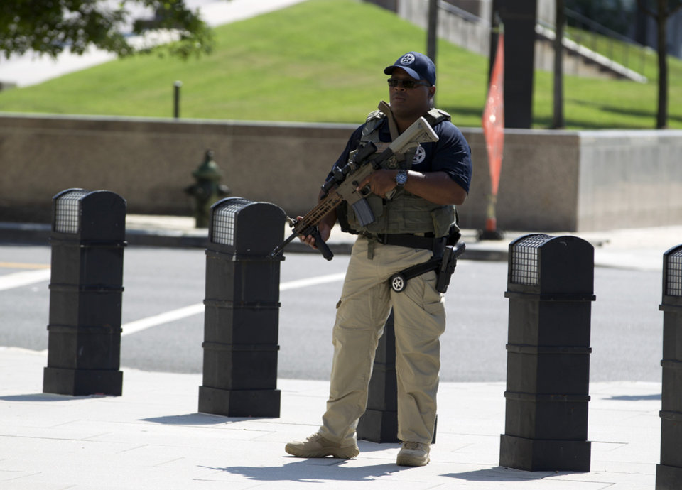 Photo - A U.S. Marshall stands guard outside of the federal U.S. District Court in Washington Saturday, June 28, 2014, after security outside the court was heightened in anticipation of a possible court appearance by captured Libyan militant Ahmed Abu Khattala later in the day. Khatallah is one of the men accused in the deadly Benghazi attack at the U.S. embassy in Libya. He faces criminal charges in the deaths of the US ambassador to Libya and three other Americans from the Sept. 11, 2012, attack. (AP Photo/Jose Luis Magana)