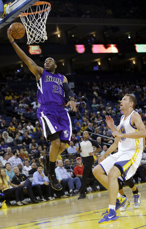 Photo - Sacramento Kings' Marcus Thornton (23) scores past Golden State Warriors' David Lee (10) during the first half of an NBA preseason basketball game Monday, Oct. 7, 2013, in Oakland, Calif. (AP Photo/Marcio Jose Sanchez)