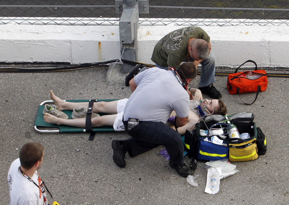 Photo - An injured spectator is treated after a crash at the conclusion of the NASCAR Nationwide Series auto race Saturday, Feb. 23, 2013, at Daytona International Speedway in Daytona Beach, Fla. Driver Kyle Larson's car hit the safety fence sending car parts and other debris flying into the stands. (AP Photo/David Graham)