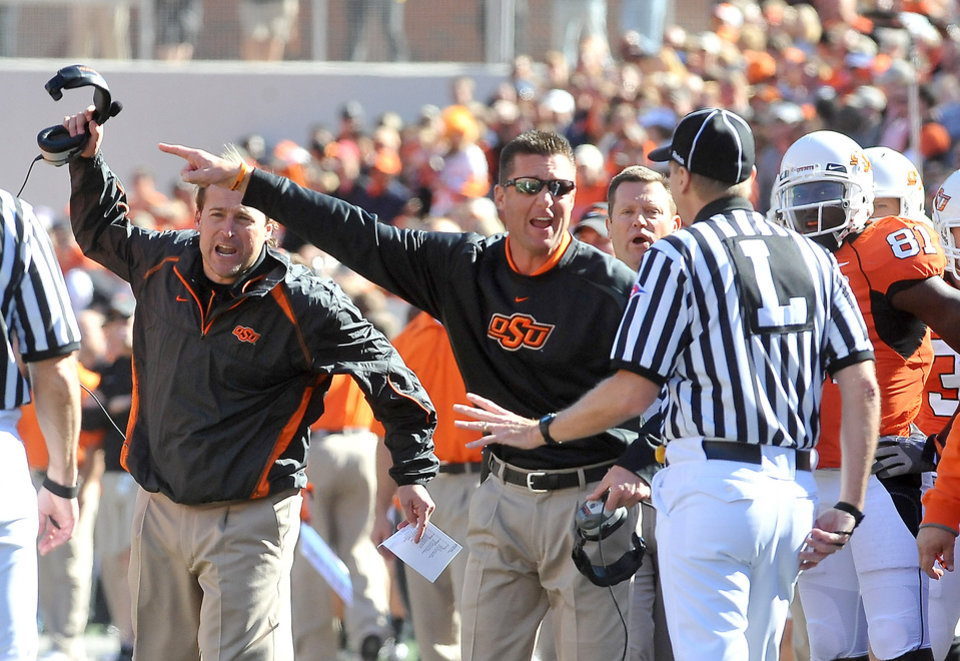Oklahoma State University offensive coordinator Dana Holgorsen, left, and head coach Mike Gundy argue with referees over a call during an NCAA college football game against Baylor, Saturday, Nov. 6, 2010, in Stillwater, Okla. (AP Photo/The News Press, Chelcey Adami)