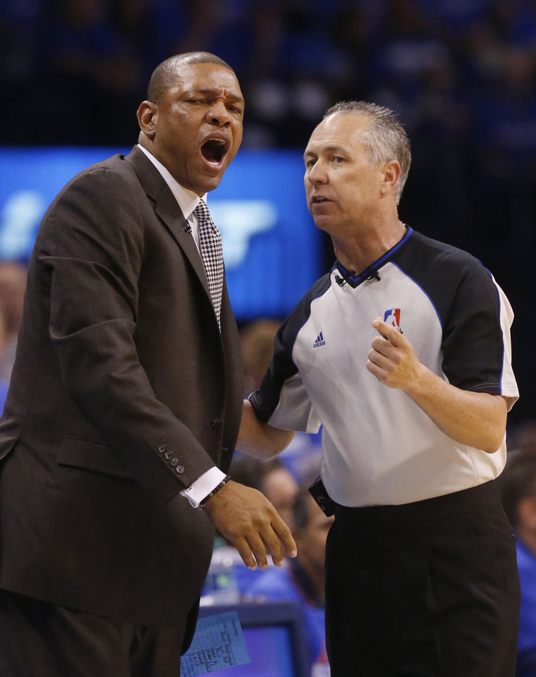 Photo - Los Angeles Clippers head coach Doc Rivers, left, reacts to a call by official Eric Lewis, right, in the first quarter of Game 1 of the Western Conference semifinal NBA basketball playoff series against the Oklahoma City Thunder in Oklahoma City, Monday, May 5, 2014. (AP Photo/Sue Ogrocki)