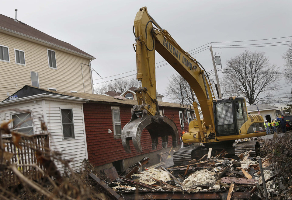 A home that was severely damaged by Superstorm Sandy is demolished in the Staten Island borough of New York, Monday, Jan. 14, 2013. Several Staten Island homes damaged beyond repair by Superstorm Sandy are being demolished. The first city-facilitated demolitions started Monday. (AP Photo/Seth Wenig)