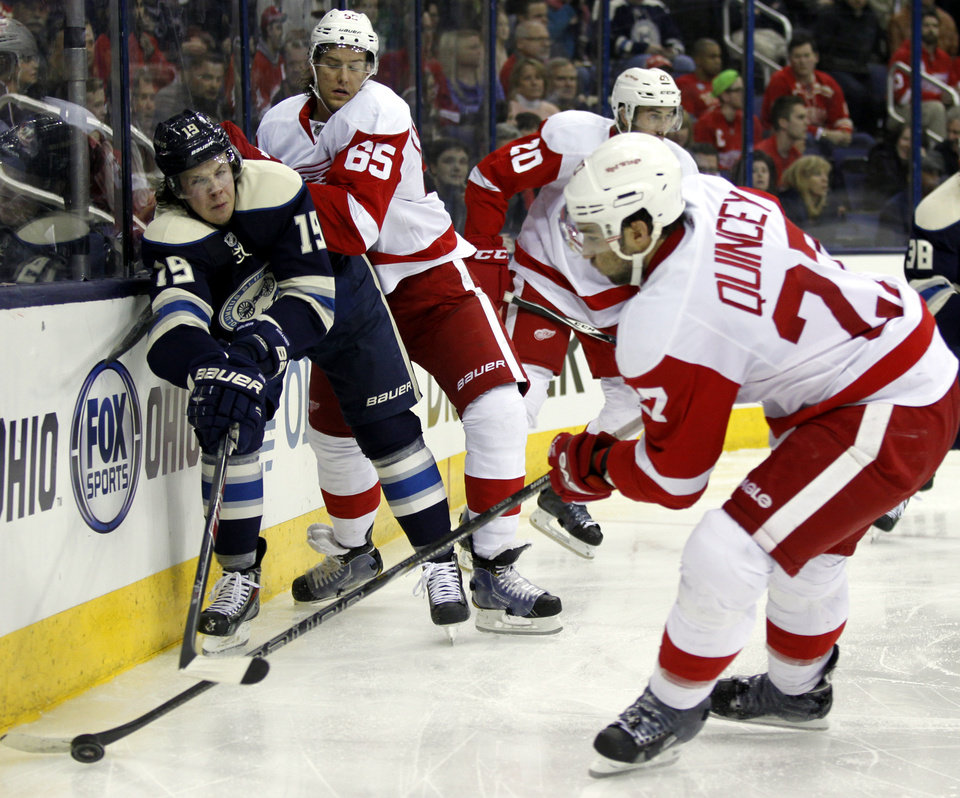 Photo - Columbus Blue Jackets' Ryan Johansen (19) works for the puck against Detroit Red Wings' Danny DeKeyser (65) and Kyle Quincey (27) in the third period of an NHL hockey game in Columbus, Ohio, Tuesday, March 25, 2014. (AP Photo/Paul Vernon)