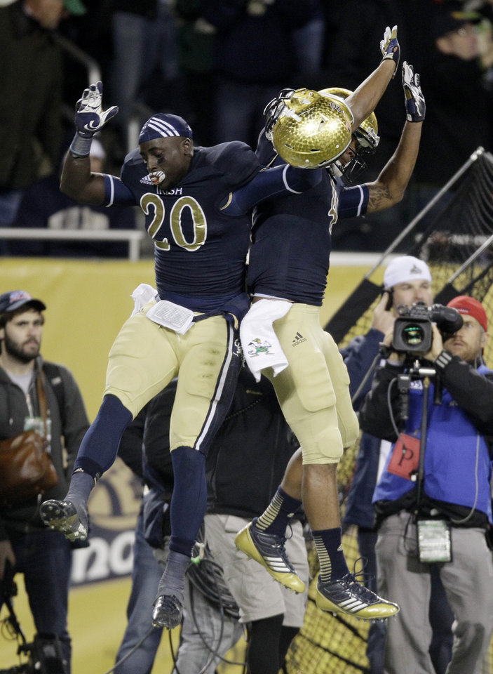 Photo -   Notre Dame running back Cierre Wood (20) and running back George Atkinson III, celebrate Woods touchdown during the second half of an NCAA college football game against Miami at Soldier Field Saturday, Oct. 6, 2012, in Chicago. (AP Photo/Nam Y. Huh)