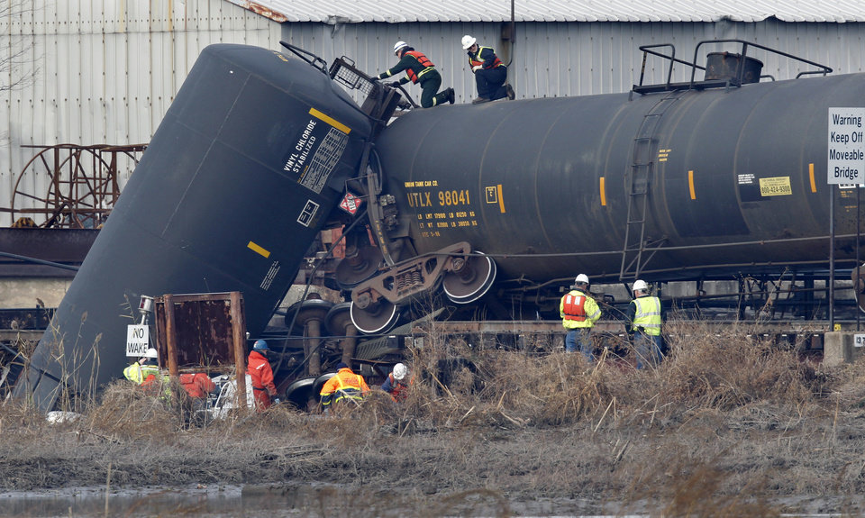 Officials examine a derailed freight train tank car in Paulsboro, N.J., Friday morning, Nov. 30, 2012. People in three southern New Jersey towns were told Friday to stay inside after a freight train derailed and several tanker cars carrying hazardous materials toppled from a bridge and into a creek. At least one tanker car may contain vinyl chloride, Gloucester County Emergency Management director J. Thomas Butts told WPVI-TV. (AP Photo/Mel Evans)