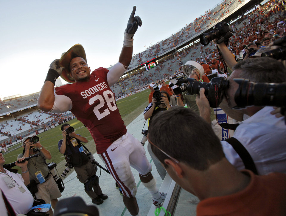 Photo - Oklahoma's Travis Lewis (28) salutes the fans while wearing the golden hat trophy after the Sooners' 28-20 win over Texas in the Red River Rivalry college football game between the University of Oklahoma Sooners (OU) and the University of Texas Longhorns (UT) at the Cotton Bowl on Saturday, Oct. 2, 2010, in Dallas, Texas.   Photo by Chris Landsberger, The Oklahoman