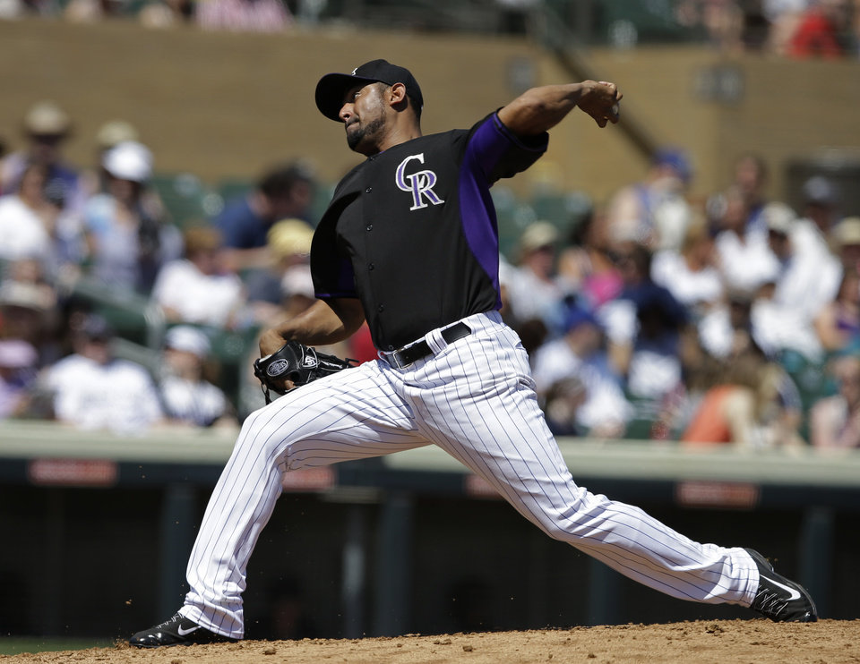 Photo - Colorado Rockies starting pitcher Franklin Morales throws during the first inning of a spring exhibition baseball game against the Seattle Mariners, Saturday, March 29, 2014, in Scottsdale, Ariz. (AP Photo/Darron Cummings)