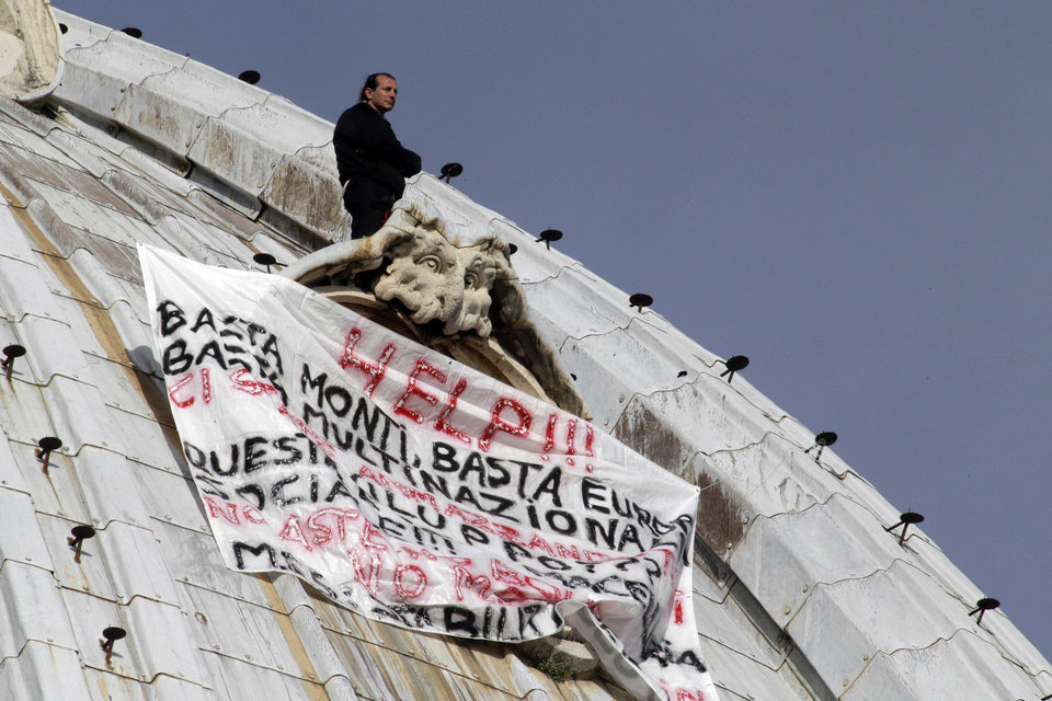 "Italian businessman Marcello di Finizio stands above his banner which reads in Italian ""Help!! Enough Monti (Italian Premier Mario Monti), enough Europe, enough multinationals, you are killing all of us. Development?? This is a social butchery!!"", as he protests on St. Peter's 130-meter-high (42-feet-high) dome, at the Vatican, Wednesday, Oct. 3, 2012. An Italian man has eluded Vatican security and scaled the 130-meter-high (42-feet-high) dome of St. Peter's Basilica to protest Italian government and European Union policies. Officials said Wednesday that the man, who identified himself as the owner of a beach resort, refused appeals from government ministers offering to meet with him if he would come down. (AP Photo/Andrew Medichini)"