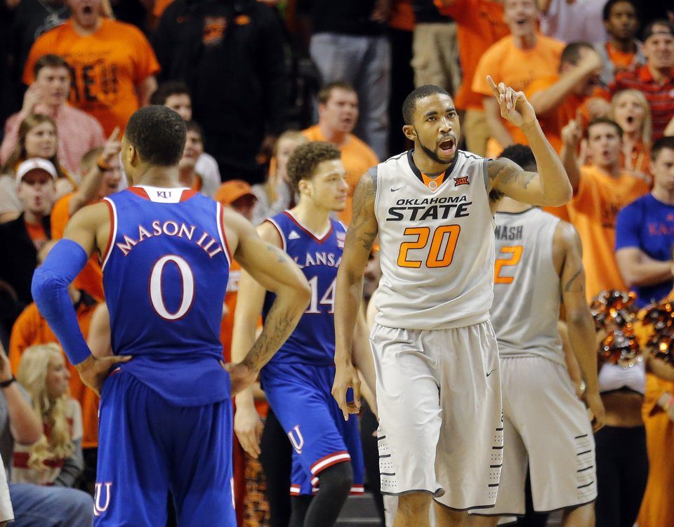 Photo - Oklahoma State's Michael Cobbins (20) celebrates next to Kansas' Frank Mason III (0) during the men's college basketball game between Oklahoma State University and the University of Kansas at Gallagher-Iba Arena in Stillwater, Okla.,  Saturday, Feb. 7, 2015. OSU won 67-62. Photo by Sarah Phipps, The Oklahoman