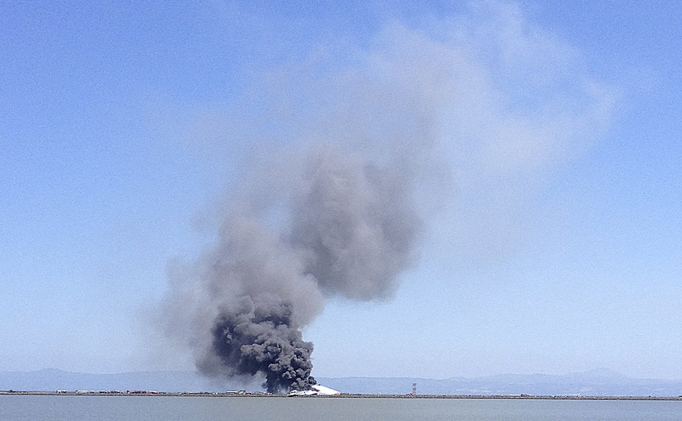 Photo - In this photo provided by Scott Sobczak, smoke rises from of Asiana Flight 214 after it crashed at San Francisco International Airport in San Francisco, Saturday, July 6, 2013. (AP Photo/Scott Sobczak) MANDATORY CREDIT