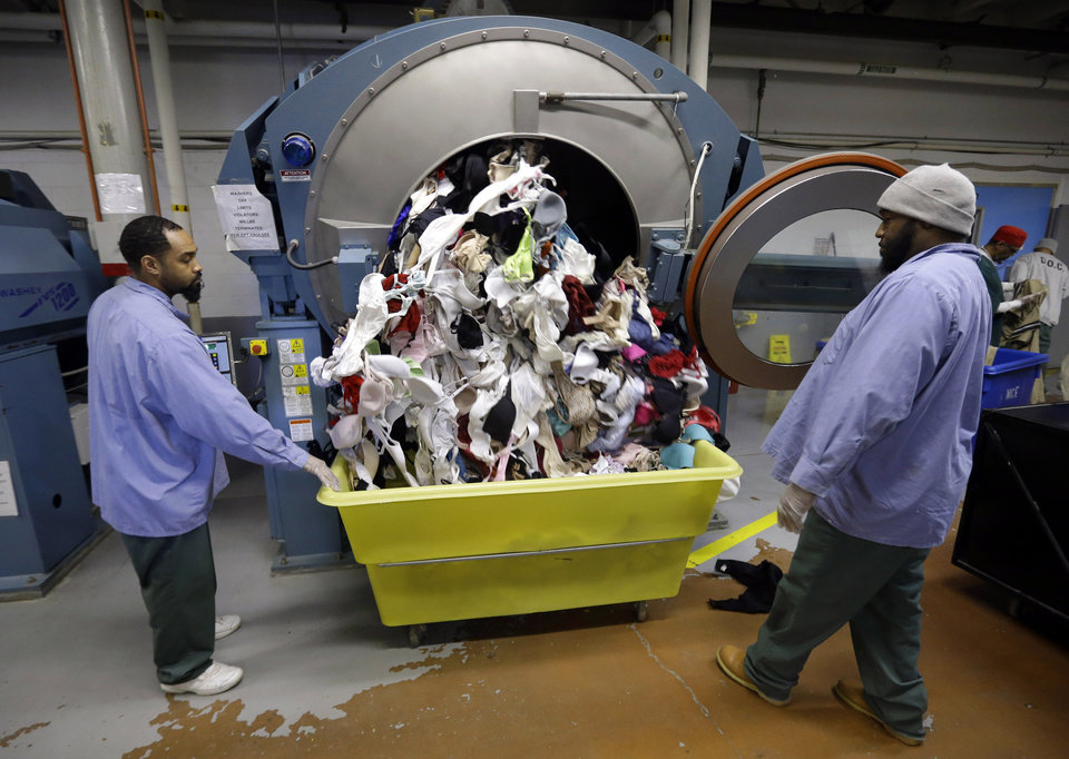 Inmates look on as bras being laundered as part of a breast cancer awareness campaign fall out of a washing machine at Central Maryland Correctional Facility in Sykesville, Md., Thursday, Dec.13, 2012. Nearly 10,000 bras were expected to be laundered by the inmates after they were collected by a radio station in Frederick, Md. One dollar for each bra was donated to breast cancer research, and the cleaned bras were expected to be donated to local women\'s shelters. Inmates at the facility annually handle more than 2.2 million pounds of laundry from state agencies and non-profit organizations in Maryland. (AP Photo/Patrick Semansky)