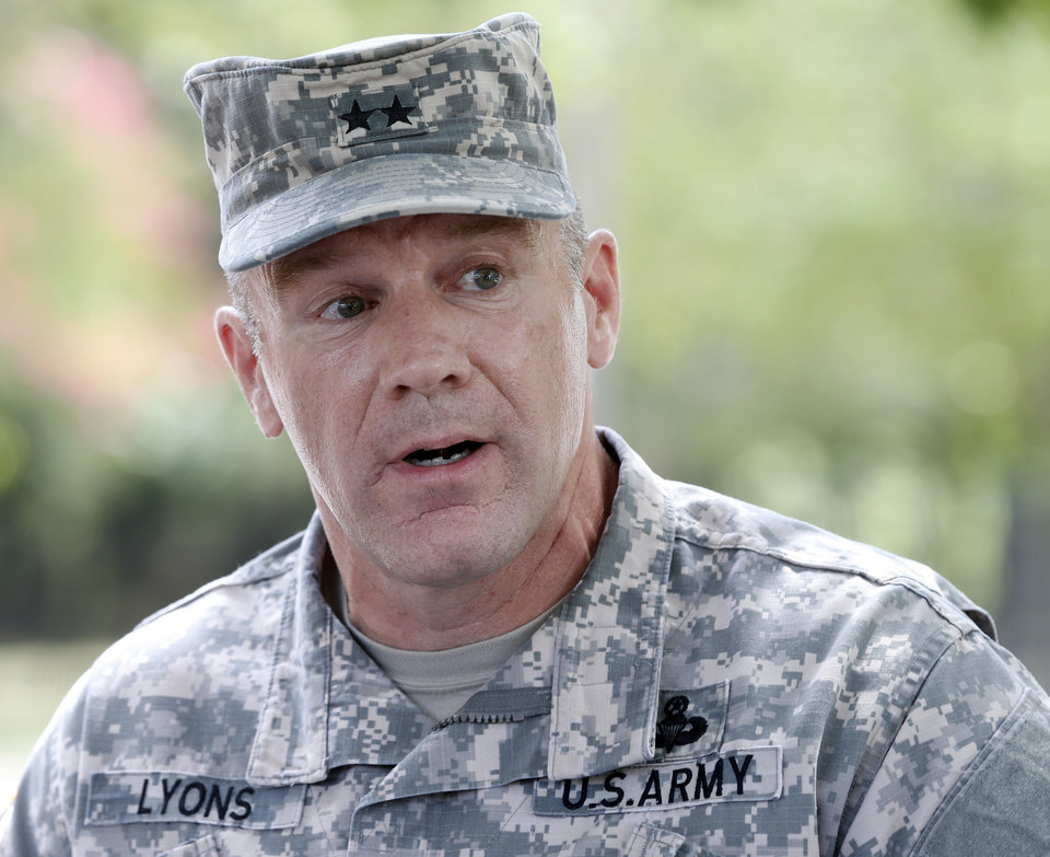 Photo - Army Maj. Gen. Stephen Lyons speaks during a news conference at the base in Fort Lee, Va., Monday, Aug. 25, 2014.  A female soldier with a gun inside a key building at the Army base turned the weapon on herself, causing an injury, but didn't wound any others as the heavily trafficked base temporarily went on lockdown Monday morning.   (AP Photo/Steve Helber)