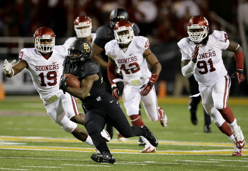 Photo - Baylor 's Shock Linwood (32) finds running room after getting past Oklahoma 's Eric Striker (19), Dominique Alexander (42) and Charles Tapper (91) in the second half of an NCAA college football game, Thursday, Nov. 7, 2013, in Waco, Texas. Baylor won 41-12.  (AP Photo/Tony Gutierrez)