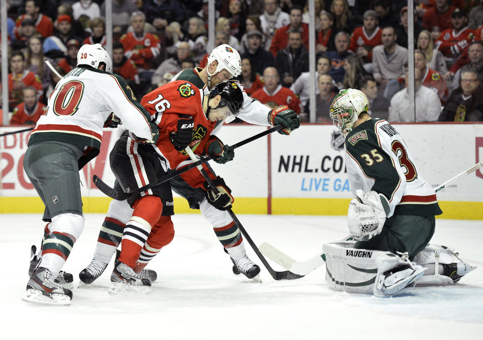 Chicago Blackhawks center Marcus Kruger of Sweden (16) tries to score as Minnesota Wild defenseman Ryan Suter, left to right, center Kyle Brodziak and goalie Darcy Kuemper defend during the second period of an NHL hockey game, Tuesday, March 5, 2013 in Chicago.  (AP Photo/Brian Kersey)