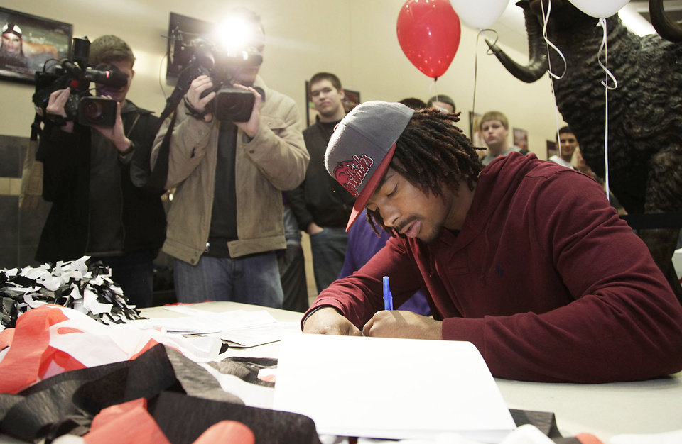 Photo - Keon Hatcher signs to play football at the University of Arkansas during signing day ceremonies at Owasso High School Feb. 1, 2012. MIKE SIMONS/Tulsa World