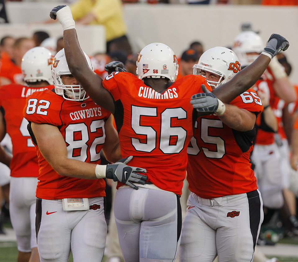 Photo - Oklahoma State's Justin Waller (82) Maurice Cummings (56) and Steve Denning (65) celebrate after the 49-45 win over Texas Tech in the college football game at Boone Pickens Stadium  on Saturday, Sept. 22, 2007, in Stillwater, Okla. 
