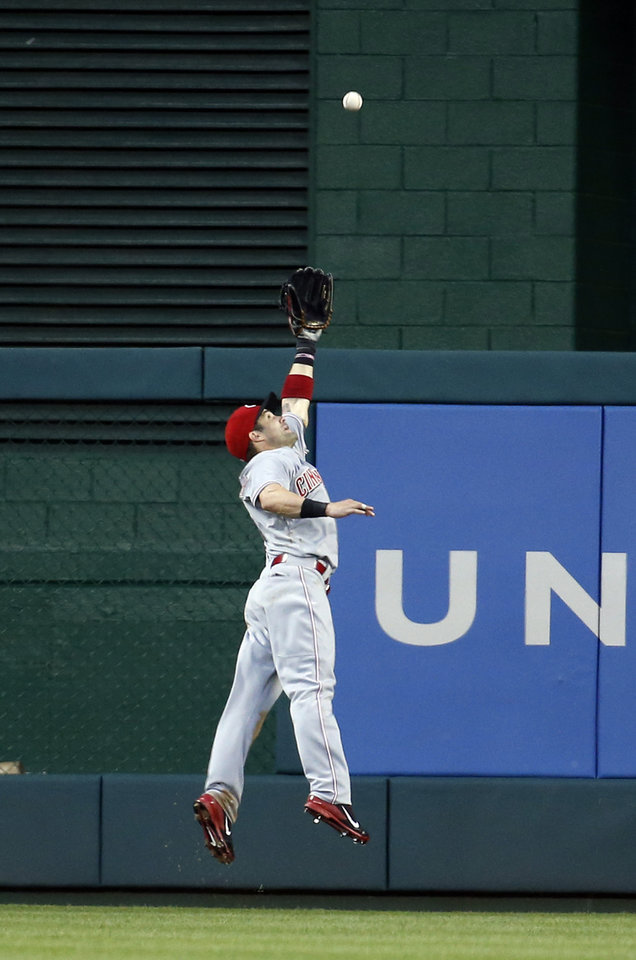 Photo - Cincinnati Reds right fielder Skip Schumaker (25) leaps but can't catch a fly ball hit by Washington Nationals' Greg Dobbs during the fourth inning of a baseball game at Nationals Park Monday, May 19, 2014, in Washington. (AP Photo/Alex Brandon)