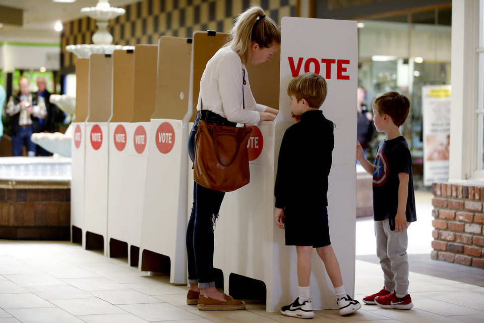 Photo - Carolyn Pursell fills out her ballot with her two sons, Hayes, 7, center, and Archer, 5, during the Super Tuesday presidential primary election inside the Shoppes at Northpark in Oklahoma City, Tuesday, March 3, 2020. [Bryan Terry/The Oklahoman]