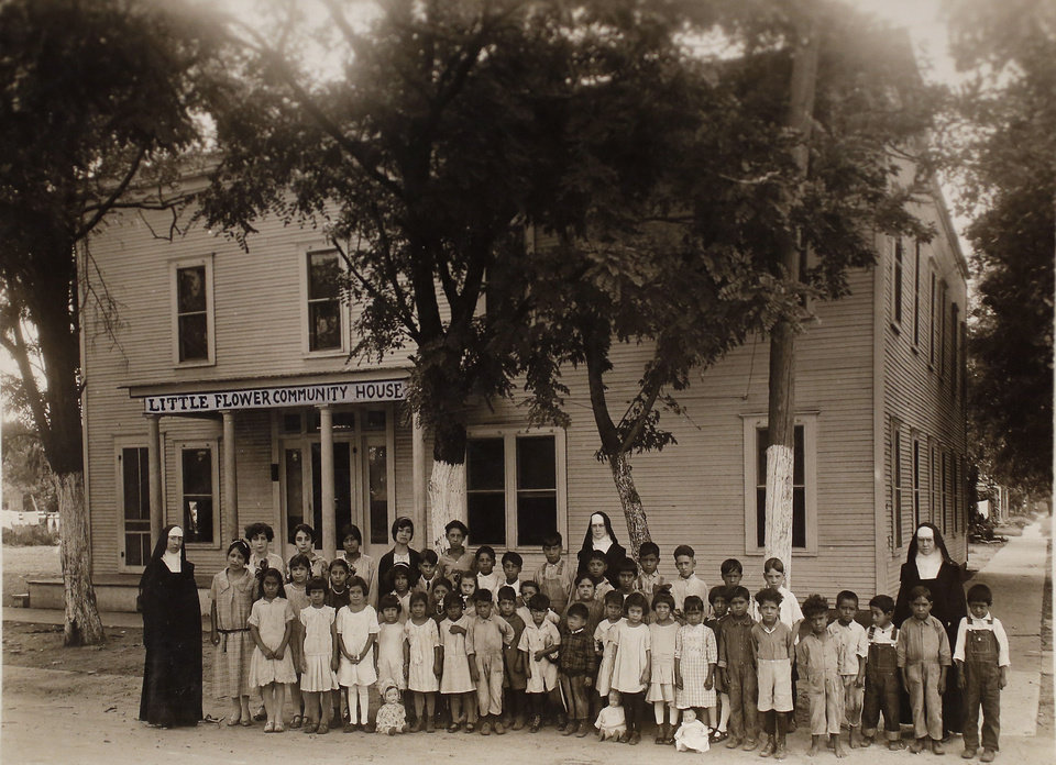 Photo - The first group of students gathers in front of Little Flower schoolhouse in September 1926. An 8-year-old Margarita Martinez is pictured in the front row on the left in the cluster of little girls. Her brother John, 6, and sister Pauline, 10, were also in this group of initial students. Photo provided by Margarita Martinez