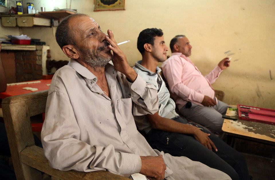 Photo - People watch an address by Iraq's Prime Minister Nouri al-Maliki on television at a cafe in Baghdad's Karrada neighborhood, Wednesday, June 25, 2014. Iraq's Shiite prime minister on Wednesday called on his nation's political blocs to close ranks in the face of a growing threat by Sunni militants who have blitzed through the country's west and north, but he gave no concrete promise of greater political inclusiveness for minority Sunnis.  (AP Photo/Karim Kadim)