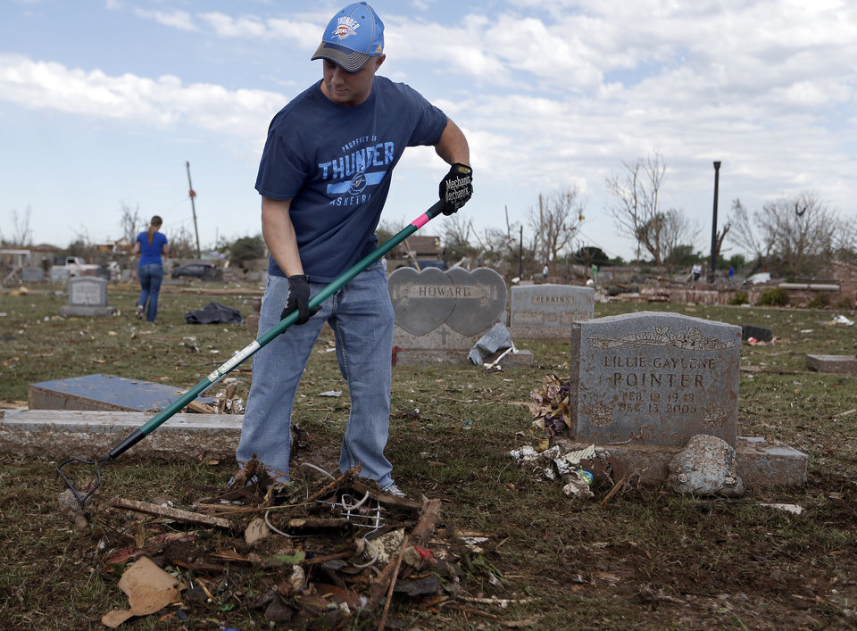 Jason Parker rakes debris at cemetery in Moore, Okla., Wednesday, May 22, 2013. Photo by Sarah Phipps, The Oklahoman