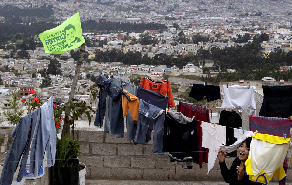 Photo - In this Jan. 28, 2013 photo, a girl plays on the terrace of her home where clothes dry where an election campaign flag flies in support of the reelection of President Rafael Correa in Quito, Ecuador. Correa is running for reelection on Sunday, Feb. 17. (AP Photo/Dolores Ochoa)