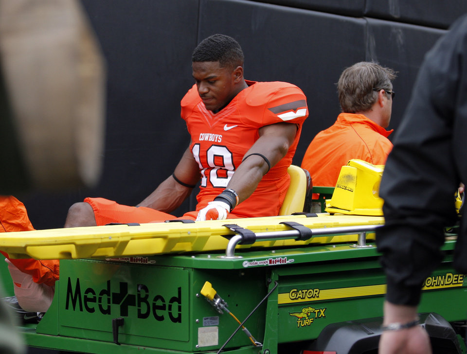 Photo - Oklahoma State's Devin Hedgepeth (18) is carted off the field during a college football game between Oklahoma State University (OSU) and the University of Louisiana-Lafayette (ULL) at Boone Pickens Stadium in Stillwater, Okla., Saturday, Sept. 15, 2012. Photo by Sarah Phipps, The Oklahoman