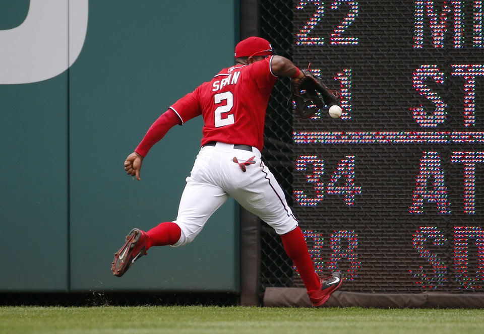 Photo - Washington Nationals center fielder Denard Span fields a ball behind his back hit for a double by Philadelphia Phillies' Cody Asche during the fifth inning of a baseball game at Nationals Park, Sunday, Aug. 3, 2014, in Washington. (AP Photo/Alex Brandon)