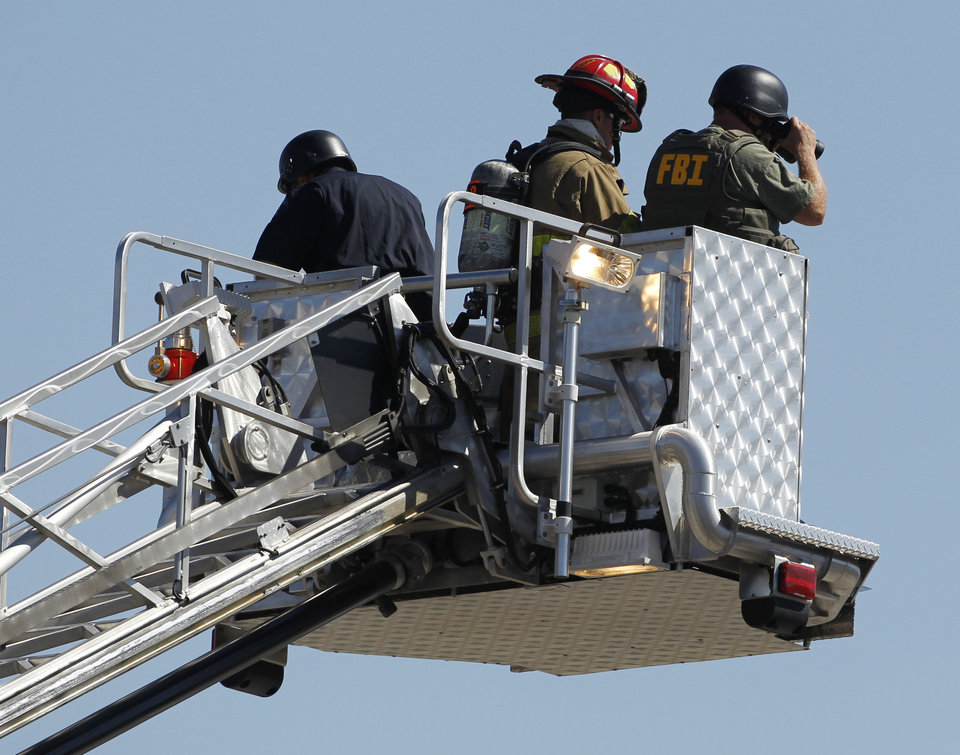 Photo - Police use the bucket on a fire truck to look down on an apartment where the suspect in a theatre shooting lived in Aurora, Colo., on Friday, July 20, 2012. As many as 12 people were killed and 50 injured at a shooting at the Century 16 movie theatre on Friday.  The suspect is identified as 24-year-old James Holmes.  (AP Photo/Ed Andrieski) ORG XMIT: COEA114