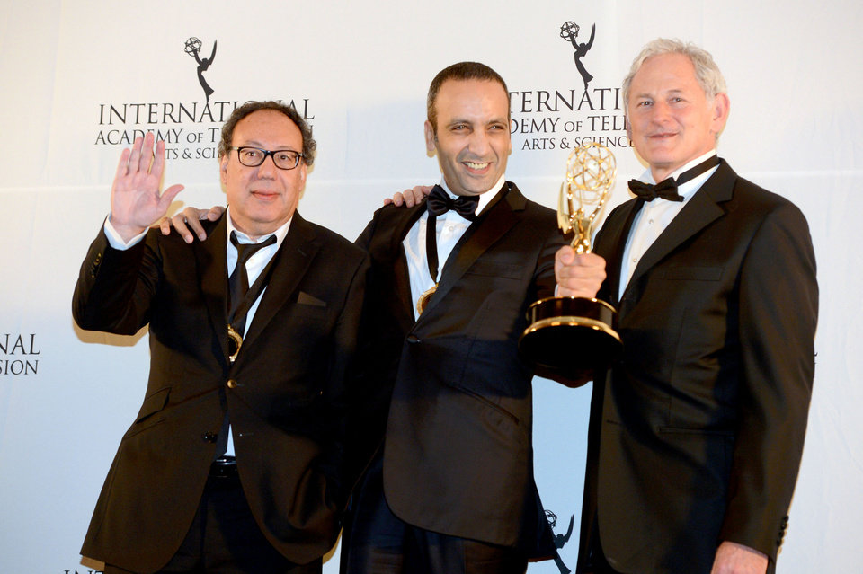 Photo -   Producer Claude Chelli, left, and writer Abdul Raouf Dafri, center, celebrate winning an International Emmy for Drama Series for