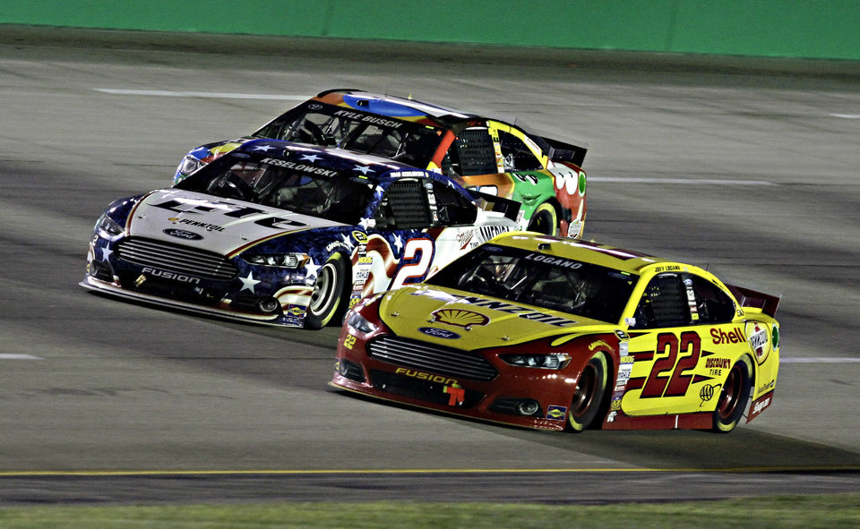 Photo - Joey Logano (22) gets a nose in front of Brad Keselowski (2) on the final restart of the NASCAR Sprint Cup series auto race Saturday, June 28, 2014, at Kentucky Speedway in Sparta, Ky. In the background is Kyle Busch. Keselowski won the race. (AP Photo/Garry Jones)