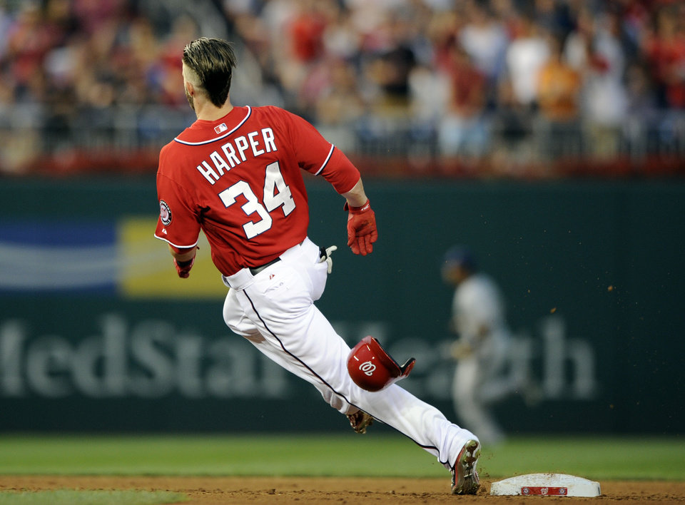 Photo - Washington Nationals' Bryce Harper rounds second on a double against the Milwaukee Brewers during the third inning of a baseball game, Saturday, July 19, 2014, in Washington. (AP Photo/Nick Wass)